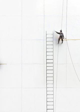 service man: Maintenance worker climbing outside a wall
