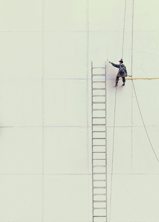 building wall: Maintenance worker drawing the ladder  outside a wall Stock Photo