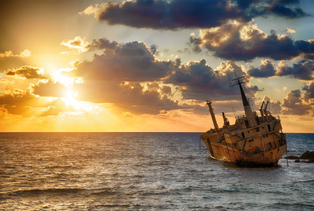 Seascape: boat EDRO III shipwrecked near the rocky shore at the sunset. Mediterranean, near Paphos. Cyprus