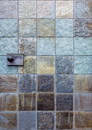 石タイルのドアノブと背景