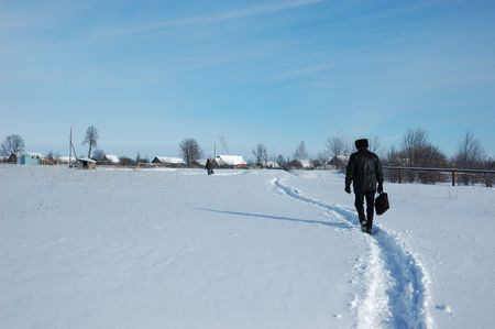 A man with a brief case, following the winter path to a small russian village, sunny winter day