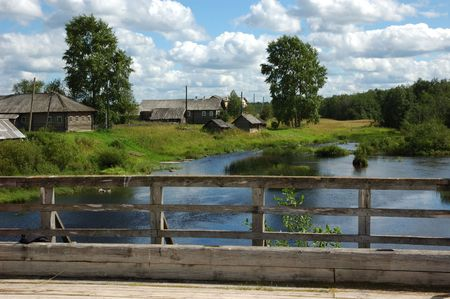 View to northern russian village by the river from wooden bridge, clouds in sky Stock Photo - 2687616
