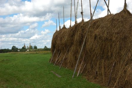 far off: Haystack on the meadow in North Russia, wooden church far off, clouds in sky
