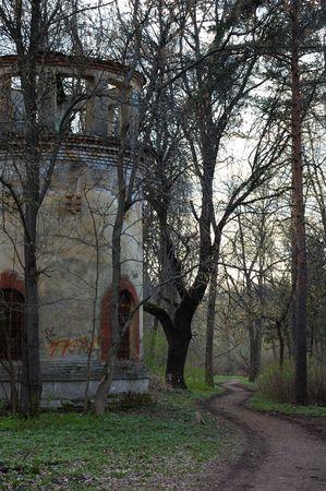 earth road: Tumbledowned torre nei pressi della strada terra nel parco vuoto Archivio Fotografico