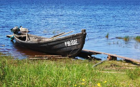 Old fishing wooden motor boat near the lake bank in north