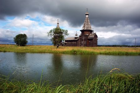 Ancient wooden russian church beyond the river, storm-clouds in sky, north Russia Stock Photo - 2784083
