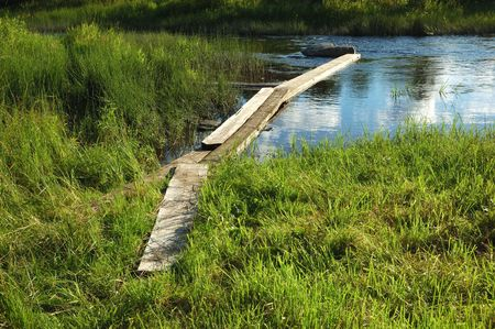 footway: Planked footway across the creek, green grass around Stock Photo