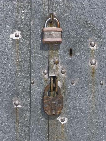 Two padlocks on galvanized iron garage gate photo