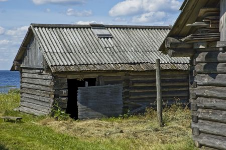 Old wooden cowshed on the lake bank, northern russian village photo