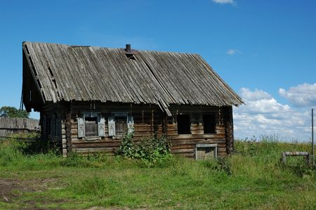 Single destroyed wooden house in field with old wooden draw-well Stock Photo - 4689671