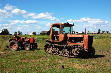 Two old tractors on the meadow at dinner-time photo