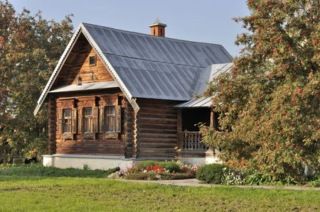 Beautiful brown wooden house with porch, flower bed and rowan-trees in autumn, Russia