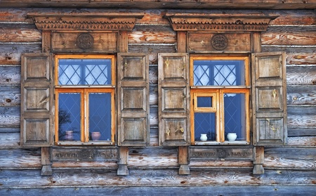 Close up of two windows with wooden shutter in old russian country house Standard-Bild