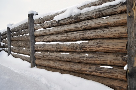 Old country log fence in winter time, Russia photo