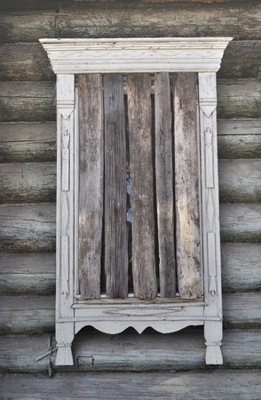 Close up of old boarded-up window in abandoned wooden house Stock Photo