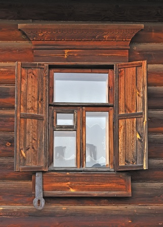 log wall: Close up of window with wooden shutter in russian country house Stock Photo