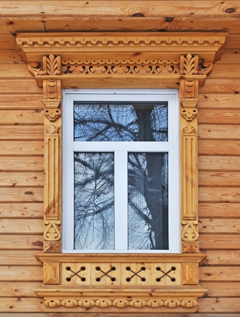 Carving decorated window in new country wooden house, Russia Standard-Bild