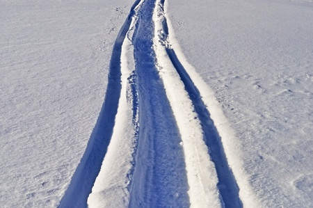 Track of snowmobile in deep snow, sunny winter day