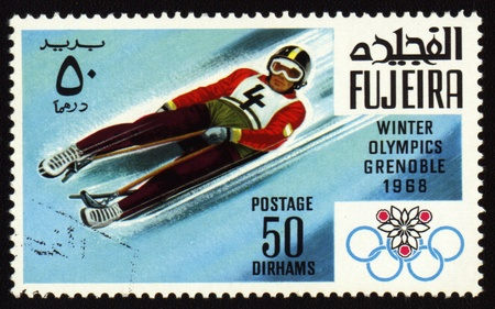 Postage stamp from Fujeira shows Winter Olympic Games in Grenoble 1968. Descent to sledge Editorial