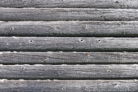 Fragment of old log wall background of abandoned wooden house