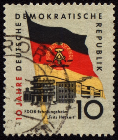 holiday home: GDR - CIRCA 1959: un sello impreso en la Rep�blica Democr�tica Alemana (Alemania Oriental), muestra su casa de vacaciones y el Estado del pabell�n de la Rep�blica Democr�tica Alemana, alrededor del a�o 1959