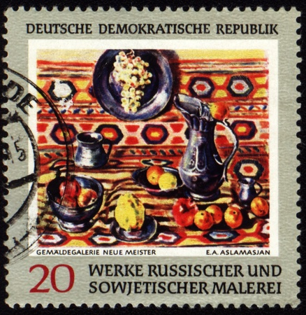 GDR - CIRCA 1960s: A stamp printed in GDR (East Germany) shows picture of a Soviet artist Aslamasyan, circa 1960s photo