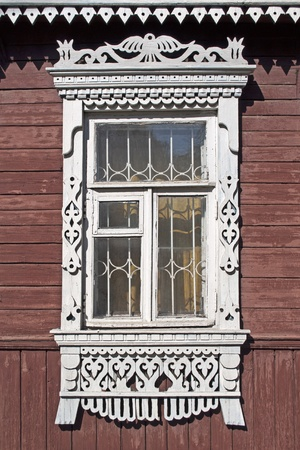 Carved window in old russian wooden country house photo