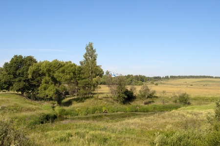 Rural landscape with a small river and sloping field photo