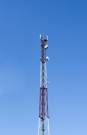 Top of a cellular tower on blue sky background photo