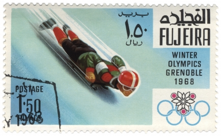 fujeira: Fujeira - CIRCA 1968  A stamp printed in Fujeira shows downhill on a sled, devoted to the Winter Games in Grenoble, series, circa 1968