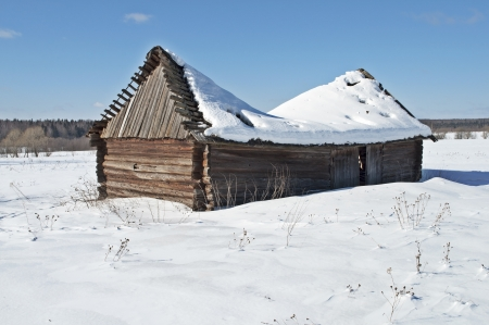 Old wooden barn with a snow-covered sagging roof, winter sunny day