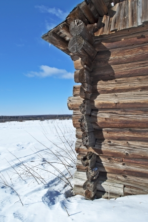 Village outskirts and corner of old log barn, winter sunny day photo