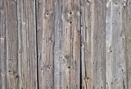 Fragment of weathered rough uncolored wooden boards background photo
