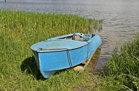 Old aluminum boat in grass by the lake