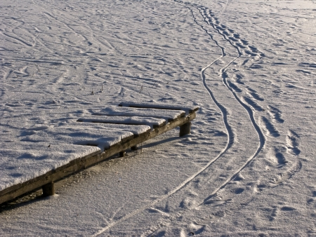footway: Wooden footway and footsteps on frozen pond on sunny winter day