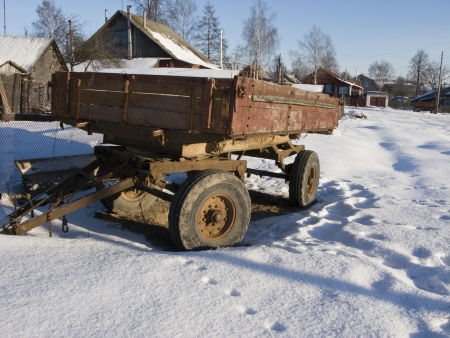 Abandoned rusty farm trailer under snow in russian village photo