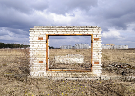 Unfinished garage gate on city outskirts background, cloudy spring day photo