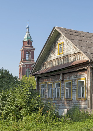 campanile: Old wooden house on a background of the bell tower, sunny summer morning Stock Photo