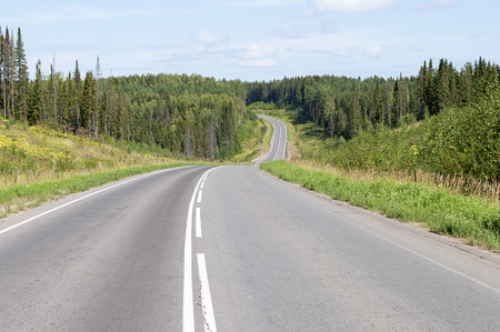 Asphalt road across the forest and hills