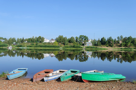 windless: Row boats on the bank of Sukhona river in Totma town, Northern Russia. Quiet windless morning Stock Photo