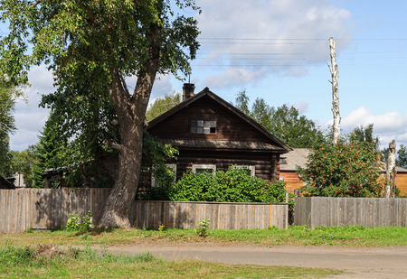 Old log house with a tall tree and unpainted wooden fence in front of him photo