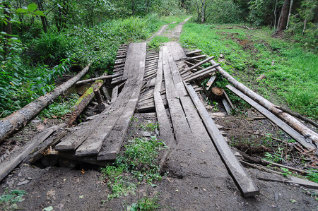wooden bridge: Dilapidated wooden bridge over a stream in the forest road