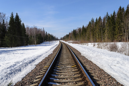 forest railroad: Railroad through the snow-covered forest clearing in early spring