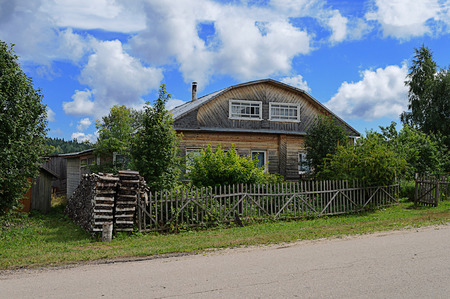 unpainted: Old unpainted wooden house in russian village with a stack of firewood, summer time Stock Photo