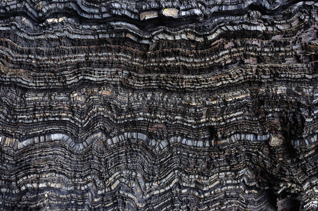 rock layers: Texture of wavy layers of black rock