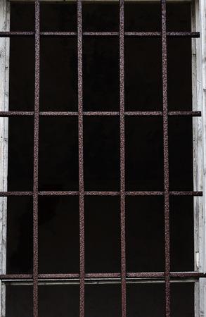 rejas de hierro: Ventana con barras de hierro para la protección de un antiguo edificio Foto de archivo