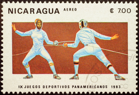rapier: MOSCOW, RUSSIA - JANUARY 21, 2016: A stamp printed in Nicaragua shows duel of two fencers, series The 9th Pan American Games, 1983