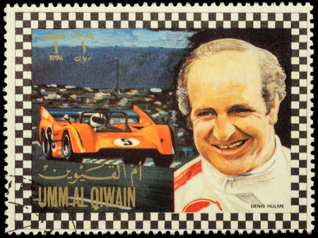 formula one racing: MOSCOW, RUSSIA - FEBRUARY 14, 2016: A stamp printed in Umm al-Quwain shows Denis Clive Denny Hulme - New Zealand racing driver in Formula One, series, circa 1972