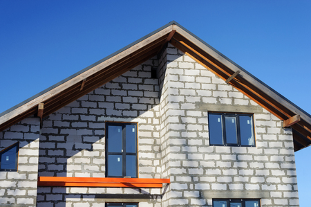 garret: Top of the unfinished white block bricks cottage on blue sky background, sunny day Stock Photo