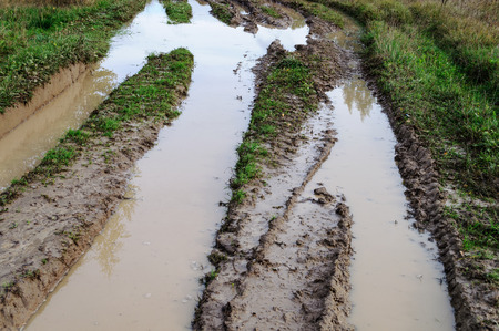 muddy: Muddy water in a deep rut of country dirt road after rain Stock Photo
